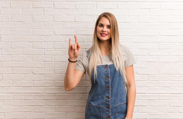 Mujer joven inconformista ruso haciendo un gesto de rock