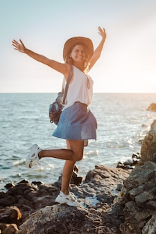 Una mujer joven inconformista en un sombrero y un rukzak con las manos en alto, de pie sobre un acantilado y mirando el mar al atardecer.