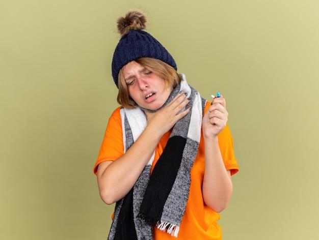 Mujer joven insalubre con sombrero con bufanda alrededor de su cuello sintiéndose mal sosteniendo diferentes pastillas que sufren de gripe y dolor de garganta tocando su cuello de pie sobre una pared verde