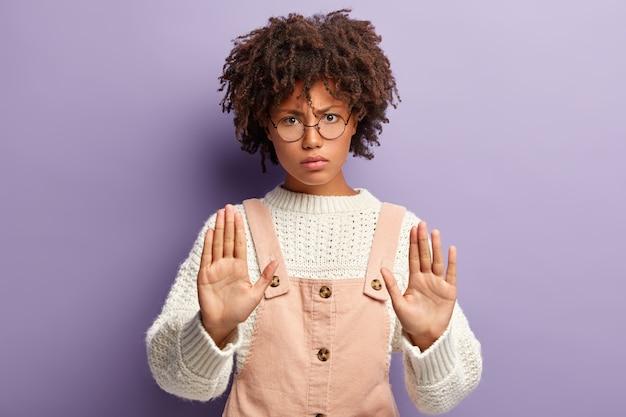 Mujer joven insatisfecha con piel oscura, cabello rizado, hace gesto de parada, tiene expresión facial enojada