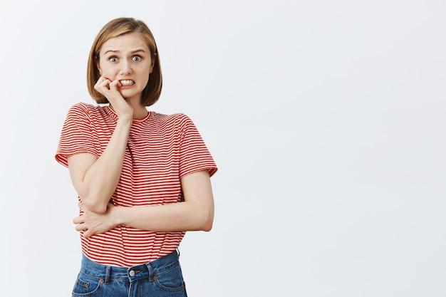 Mujer joven insegura y alarmada mordiéndose la uña y sintiéndose preocupado