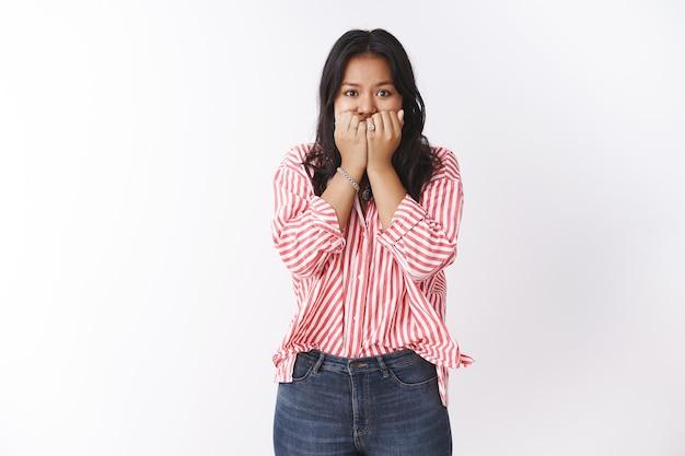 Mujer joven insegura asustada de ser despedida de pie preocupada y asustada mordiéndose las uñas sosteniendo los brazos cerca de la boca con aspecto perturbado y nervioso ante la cámara, sintiendo ansiedad sobre la pared blanca