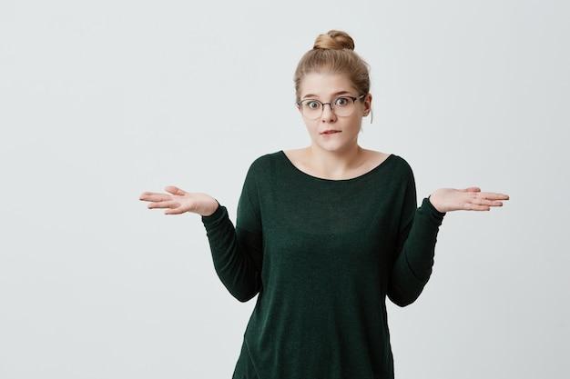 Mujer joven insegura y desorientada con una apariencia atractiva, moño de cabello rubio, hombros encogidos, duda si ir con amigos a caminar o estudiar y prepararse para los exámenes. percepción de la vida