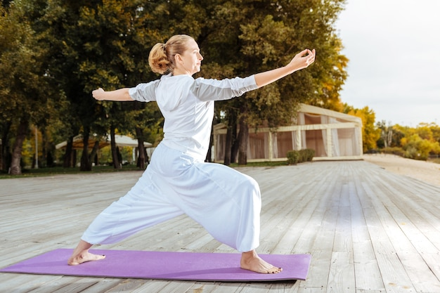 Mujer joven inspirada practicando asanas de yoga cerca del agua