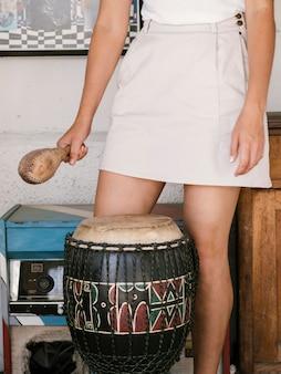 Mujer joven con instrumentos de percusión a su alrededor.
