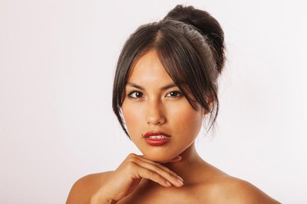 Mujer joven interesante posando con una mano bajo la barbilla