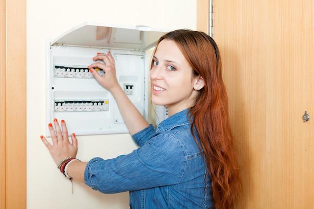 Mujer joven con el interruptor de la luz en el hogar