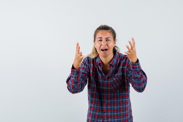 Mujer joven invitando a entrar en camisa a cuadros y mirando agotado
