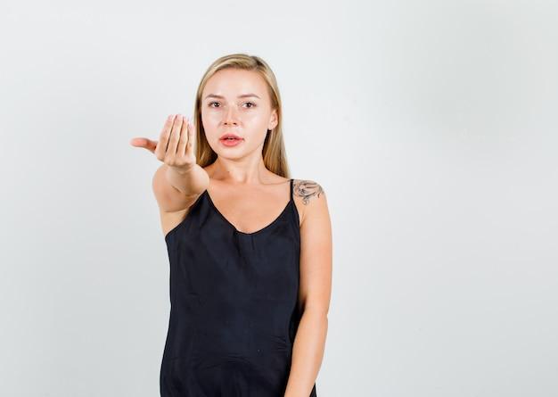 Mujer joven invitando a venir con la mano en camiseta negra