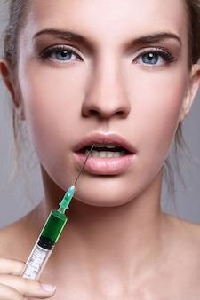 Mujer joven inyectando para un tratamiento de belleza