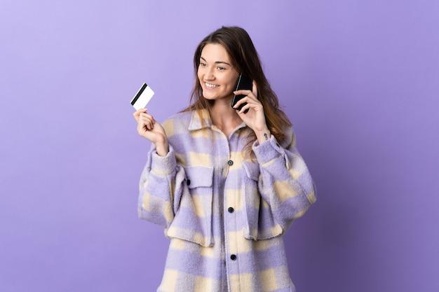 Mujer joven de irlanda aislada sobre fondo púrpura manteniendo una conversación con el teléfono móvil y sosteniendo una tarjeta de crédito