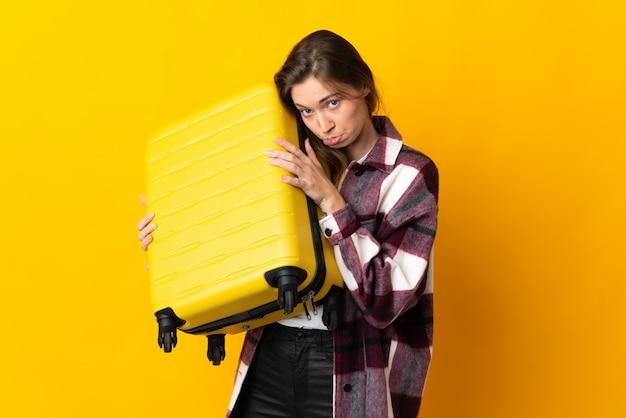 Mujer joven de irlanda aislada en vacaciones con maleta de viaje e infeliz
