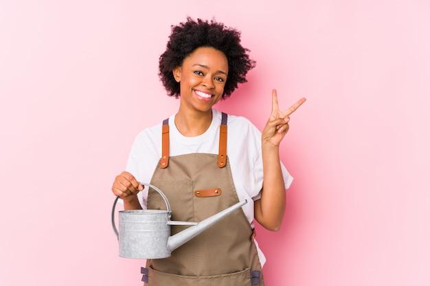 Mujer joven jardinero afroamericano alegre y despreocupado mostrando un símbolo de paz con los dedos.