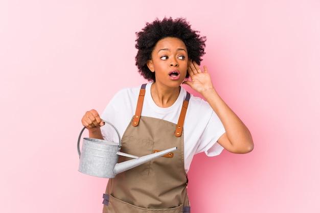 Mujer joven jardinero afroamericano tratando de escuchar un chisme.