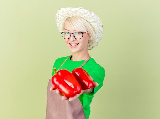 Mujer joven jardinero con pelo corto en delantal y sombrero mostrando pimientos rojos con sonrisa en la cara