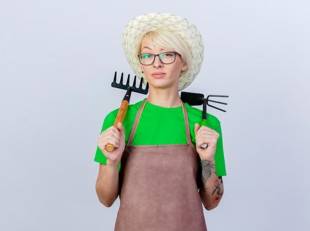 Mujer joven jardinero con pelo corto en delantal y sombrero sosteniendo azadón y mini rastrillo con cara seria