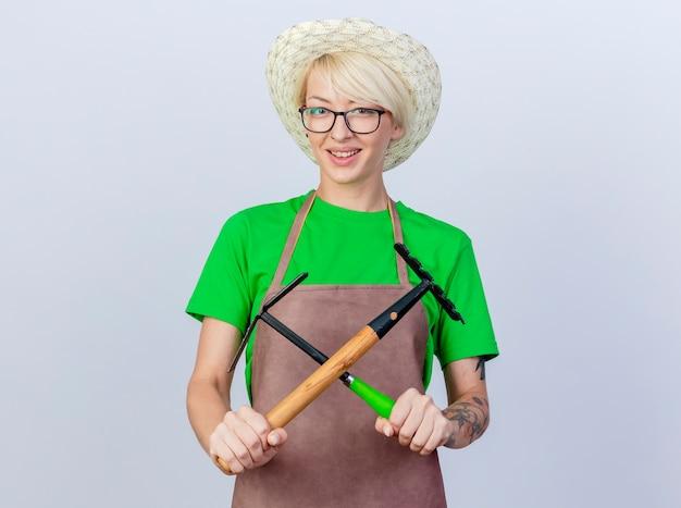 Mujer joven jardinero con pelo corto en delantal y sombrero sosteniendo azadón y mini rastrillo cruzando las manos sonriendo alegremente