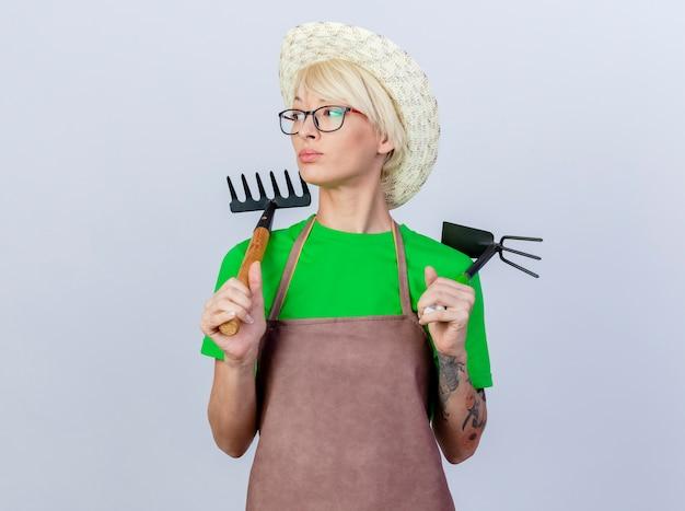 Mujer joven jardinero con pelo corto en delantal y sombrero sosteniendo azadón y mini rastrillo lookign a un lado con cara seria