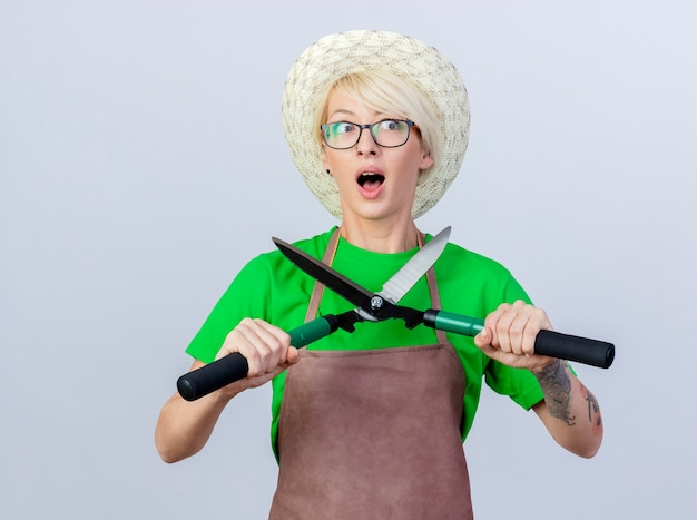 Mujer joven jardinero con pelo corto en delantal y sombrero sosteniendo cortasetos lookign a un lado siendo sorprendido