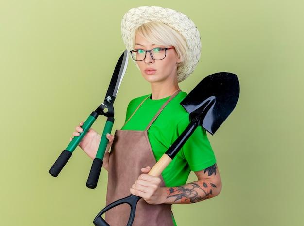 Mujer joven jardinero con pelo corto en delantal y sombrero sosteniendo equipos de jardinería mirando a cámara con rostro serio sobre fondo claro