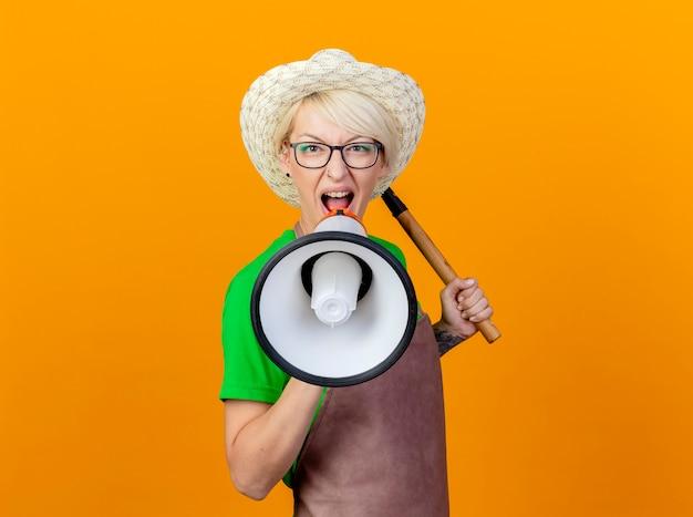 Mujer joven jardinero con pelo corto en delantal y sombrero sosteniendo mini rastrillo gritando al megáfono de pie sobre fondo naranja