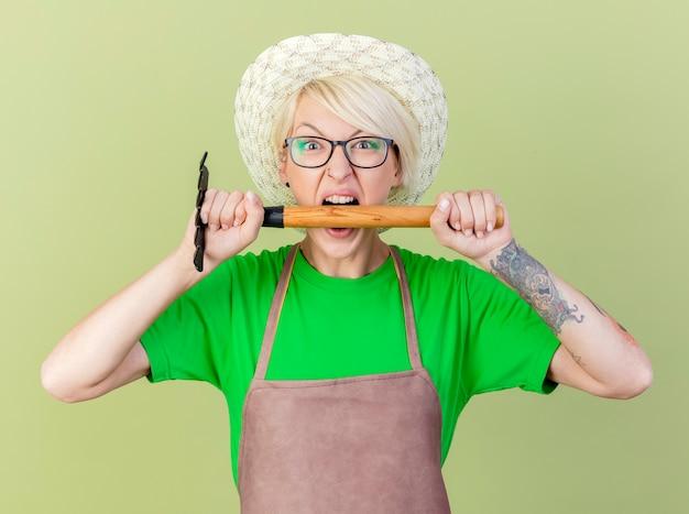 Mujer joven jardinero con pelo corto en delantal y sombrero sosteniendo mini rastrillo va a morderlo con expresión agresiva de pie sobre fondo claro