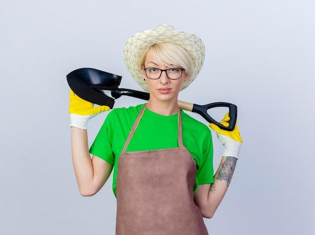 Mujer joven jardinero con pelo corto en delantal y sombrero sosteniendo pala con seria expresión de confianza