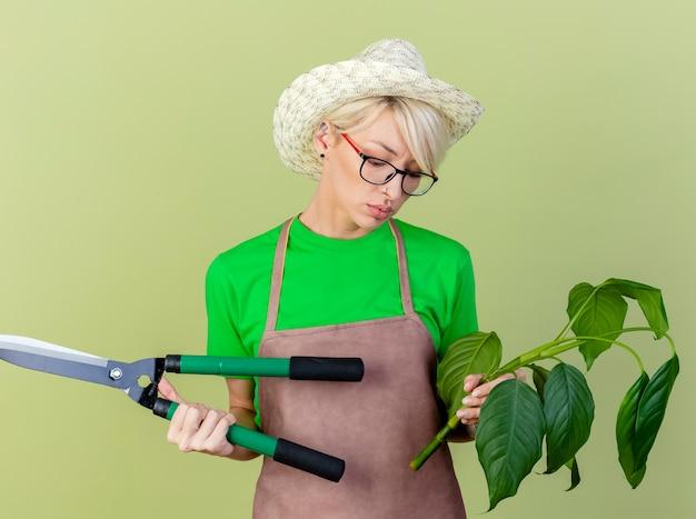 Mujer joven jardinero con pelo corto en delantal y sombrero sosteniendo planta y cortasetos mirando confundido e incierto de pie sobre fondo claro