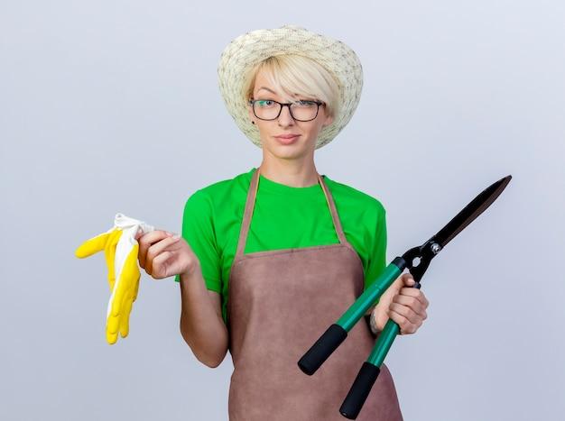 Mujer joven jardinero con pelo corto en delantal y sombrero sosteniendo podadoras de setos y guantes de goma sonriendo confiado