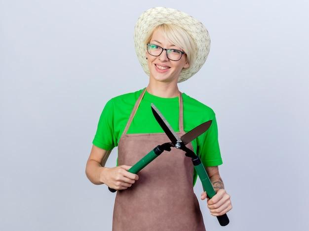 Mujer joven jardinero con pelo corto en delantal y sombrero sosteniendo podadoras de setos sonriendo alegremente feliz y positivo