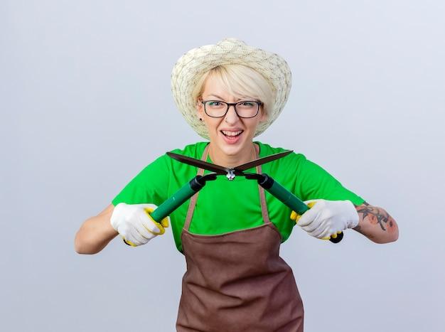 Mujer joven jardinero con pelo corto en delantal y sombrero sosteniendo podadoras de setos sonriendo alegremente