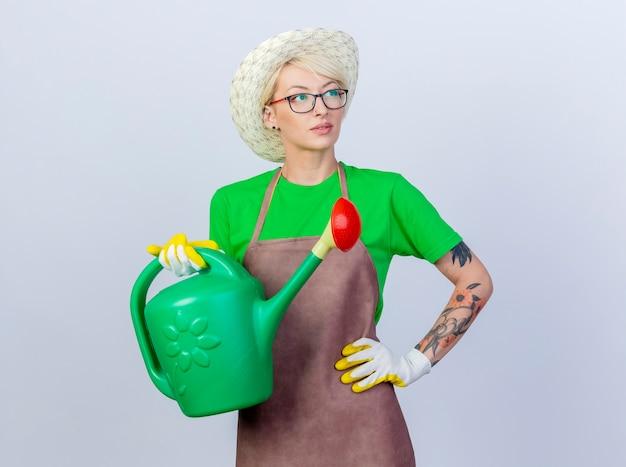 Mujer joven jardinero con pelo corto en delantal y sombrero sosteniendo regadera mirando a un lado desconcertado y pensando