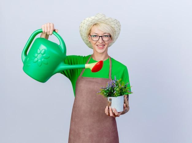 Mujer joven jardinero con pelo corto en delantal y sombrero sosteniendo regadera y planta en maceta sonriendo con cara feliz