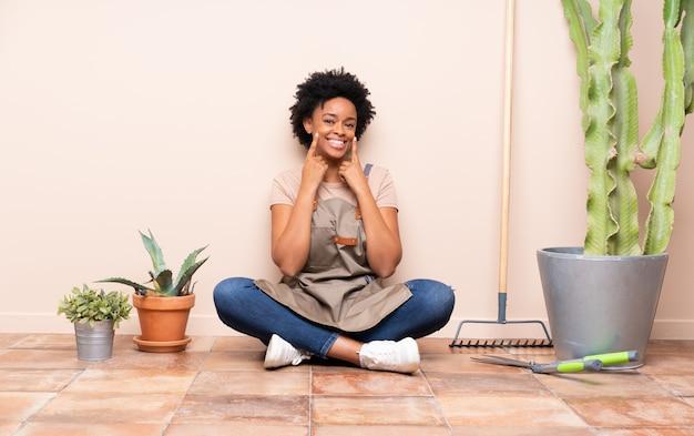 Mujer joven jardinero sentada en el suelo