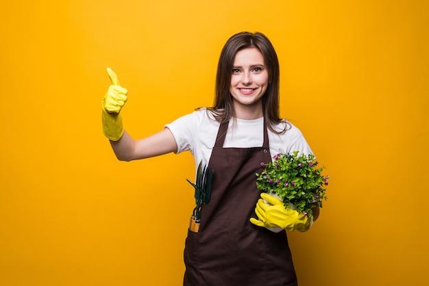 Mujer joven jardinero sosteniendo una planta dando un pulgar hacia arriba gesto