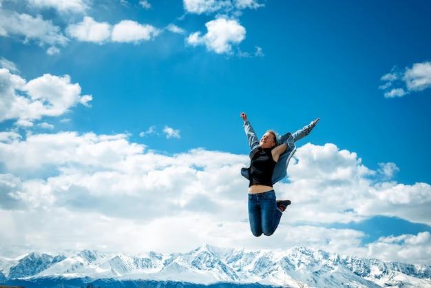 Mujer joven en jeans salta alto en el aire contra el cielo