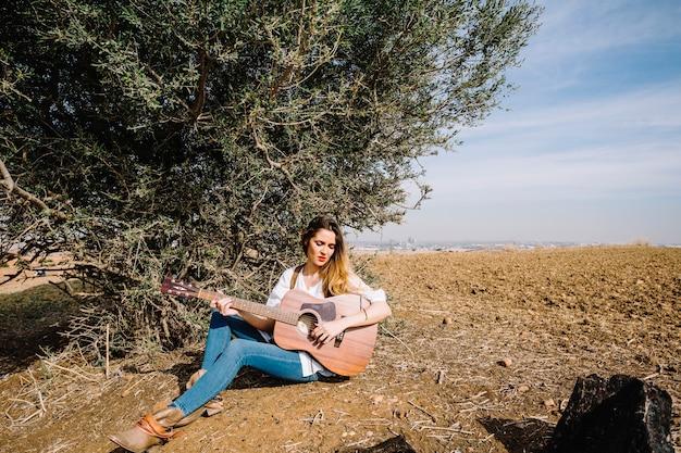 Mujer joven, juego, guitarra, cerca, arbusto