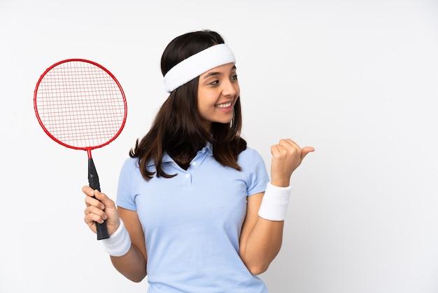 Mujer joven jugador de bádminton sobre blanco aislado apuntando hacia el lado para presentar un producto