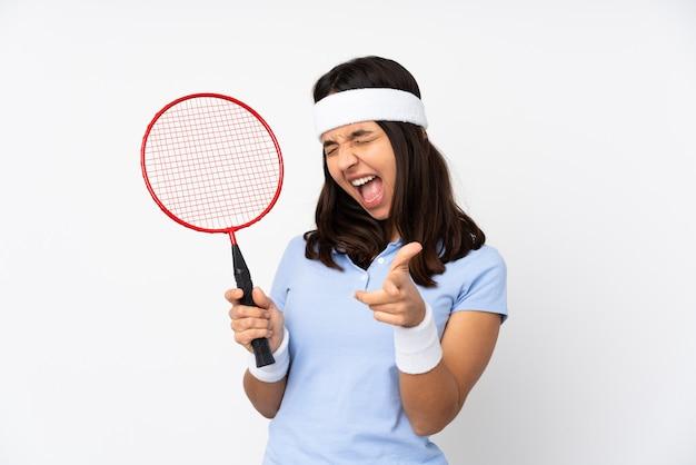 Mujer joven jugador de bádminton sobre pared blanca apuntando hacia el frente y sonriendo