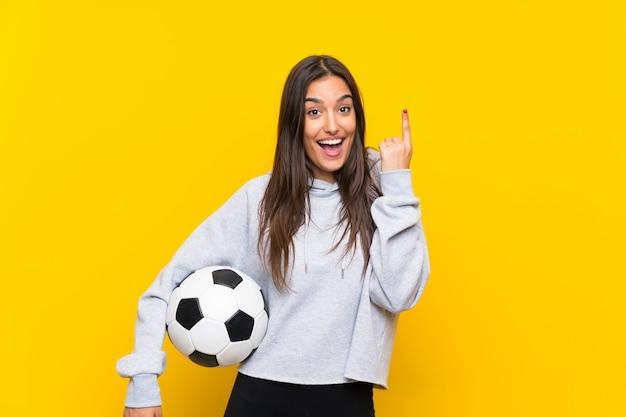Mujer joven del jugador de fútbol aislada en amarillo que señala encima de una gran idea