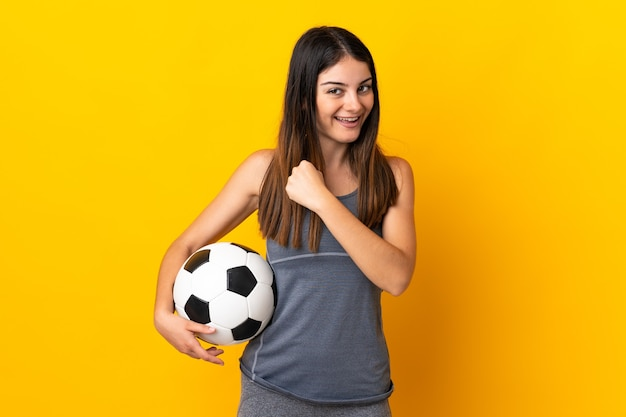 Mujer joven jugador de fútbol aislado en la pared amarilla celebrando una victoria