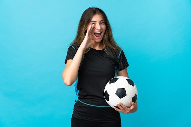 Mujer joven jugador de fútbol aislado en la pared azul gritando con la boca abierta