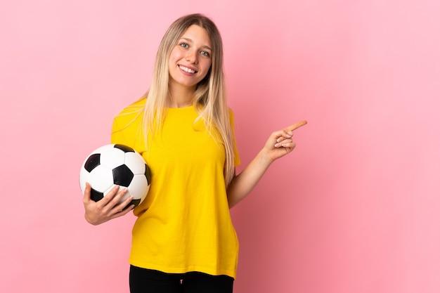 Mujer joven jugador de fútbol aislado en rosa dedo acusador hacia el lado
