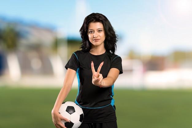 Mujer joven del jugador de fútbol que sonríe y que muestra la muestra de la victoria en al aire libre