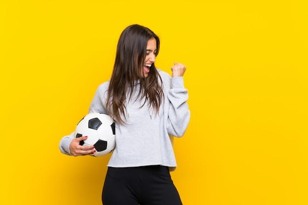 Mujer joven jugador de fútbol sobre pared amarilla aislada celebrando una victoria