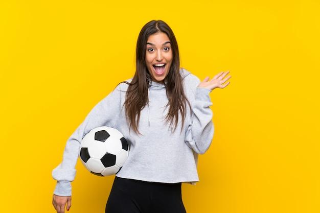 Mujer joven jugador de fútbol sobre pared amarilla aislada con expresión facial sorprendida
