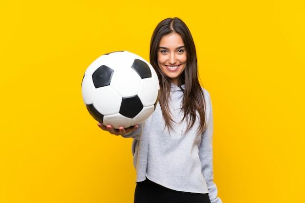 Mujer joven jugador de fútbol sobre pared amarilla aislada