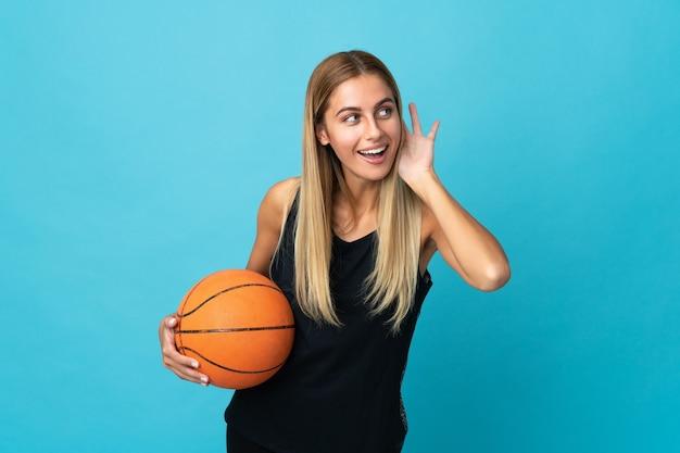 Mujer joven jugando baloncesto aislado en la pared blanca escuchando algo poniendo la mano en la oreja