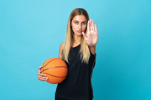 Mujer joven jugando baloncesto aislado sobre fondo blanco haciendo gesto de parada