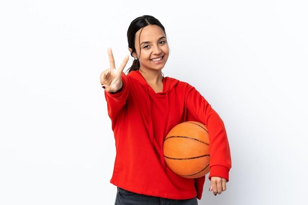 Mujer joven jugando baloncesto sobre fondo blanco aislado sonriendo y mostrando el signo de la victoria